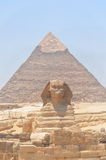The Sphinx and Pyramid in Egypt. The wonderfull and misterious Sphinx guardian of King's valley in Gizah with the Cheope's pyramid on the back Royalty Free Stock Photography