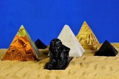 The Sphinx and pyramids in the sand on a blue background. Pyramid architecture is a symbol of eternal energy. The Sphinx is a. Mythical creature. In ancient stock photos