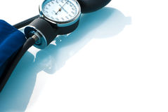 Sphygmomanometer on blue, reflective background Royalty Free Stock Images