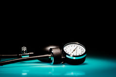 Sphygmomanometer on blue, reflective table Royalty Free Stock Image