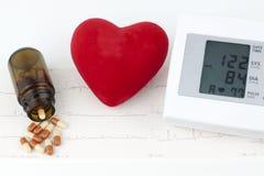 Sphygmomanometer, coeur et pilules sur une feuille d'électrocardiogramme Images libres de droits