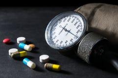 Sphygmomanometer con las píldoras de la medicina Imágenes de archivo libres de regalías