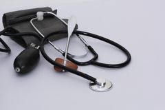 Sphygmomanometer cuff, reflex hammer and stethoscope on white ba royalty free stock photos