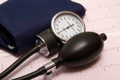 Sphygmomanometer on ECG chart Stock Photos