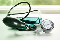 Sphygmomanometer en la tabla de funcionamiento de un tonometer de Green del cardiólogo para la presión arterial de medición imagen de archivo