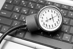 Sphygmomanometer on laptop keyboard Stock Image