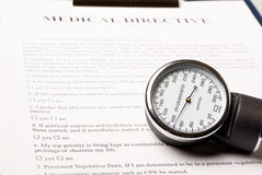Sphygmomanometer on medical directive document Stock Images