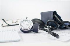 Sphygmomanometer na pracującym stole kardiolog Tonometer, elektrokardiogram i notepad dla rejestrów, obrazy stock
