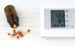 Sphygmomanometer and pills on a sheet of EKG Royalty Free Stock Photo