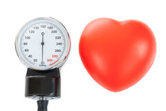A sphygmomanometer and a toy heart as symbols of health care system Stock Photos