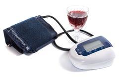 Sphygmomanometer und Glas Rotwein Lizenzfreies Stockfoto