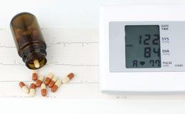 Sphygmomanometer und Pillen auf einem Blatt des EKG lizenzfreies stockfoto