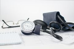 Sphygmomanometer on the working table of a cardiologist. Tonometer, electrocardiogram and notepad for records. Sphygmomanometer on the working table of a stock images