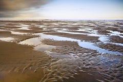 Spiaggia abbandonata alla marea bassa Fotografie Stock