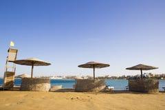 Spiaggia abbandonata con gli ombrelloni dei ramoscelli asciutti sui precedenti Fotografia Stock Libera da Diritti