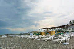 Spiaggia abbandonata con le chaise-lounge del sole con un giorno nuvoloso In attesa della stagione della spiaggia Fotografia Stock Libera da Diritti