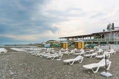 Spiaggia abbandonata con le chaise-lounge del sole con un giorno nuvoloso L'inizio della stagione della spiaggia Fotografia Stock