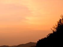 Spiaggia all'arancia del cielo di tramonto Fotografia Stock
