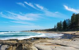 Spiaggia australiana della costa del sole con roccia vulcanica nella priorità alta e la gente ed i cani che godono del giorno sol Immagine Stock Libera da Diritti