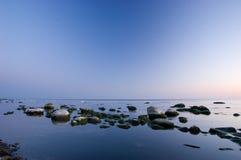 Spiaggia baltica con le pietre dopo il tramonto Immagini Stock