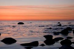 Spiaggia baltica con le pietre dopo il tramonto Immagini Stock Libere da Diritti