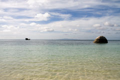 Spiaggia, barca e una roccia Fotografie Stock