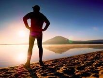 spiaggia che esercita uomo Siluetta dell'uomo attivo che si esercita e che allunga nel lago Immagini Stock Libere da Diritti
