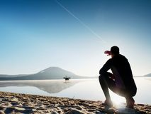 spiaggia che esercita uomo Siluetta dell'uomo attivo che si esercita e che allunga nel lago Fotografie Stock
