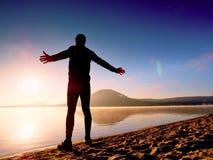spiaggia che esercita uomo Siluetta dell'uomo attivo che si esercita e che allunga nel lago Immagini Stock