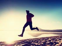 spiaggia che esercita uomo Siluetta dell'uomo attivo che si esercita e che allunga nel lago Fotografie Stock Libere da Diritti