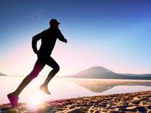 spiaggia che esercita uomo Siluetta dell'uomo attivo che si esercita e che allunga nel lago Immagine Stock