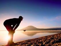 spiaggia che esercita uomo Siluetta dell'uomo attivo che si esercita e che allunga nel lago Fotografia Stock Libera da Diritti