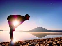 spiaggia che esercita uomo Siluetta dell'uomo attivo che si esercita e che allunga nel lago Immagine Stock Libera da Diritti