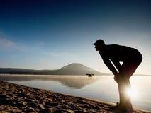 spiaggia che esercita uomo Siluetta dell'uomo attivo che si esercita e che allunga nel lago Fotografia Stock