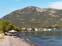 Spiaggia ciottolosa, piccolo paesino di pescatori del golfo di Corinto, Grecia Immagini Stock Libere da Diritti