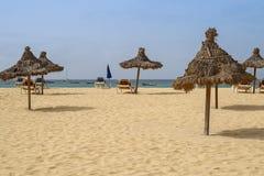 Spiaggia con gli ombrelli ed i letti della paglia fotografie stock