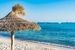 Spiaggia con l'ombrello della paglia e della spiaggia di sabbia fotografia stock libera da diritti
