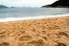 Spiaggia con la sabbia, il mare e le montagne Immagini Stock Libere da Diritti