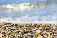 Spiaggia con le onde e Pebble Beach della sfuocatura Immagini Stock Libere da Diritti