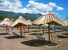 Spiaggia con le presidenze e gli ombrelli fotografia stock