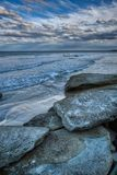 Spiaggia con le rocce ed i massi bluastri in cielo molle dei wave's dell'acqua di mare con i surfisti delle nuvole nella distan fotografia stock libera da diritti