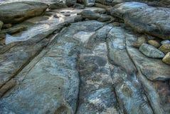 Spiaggia con le vecchie grandi rocce e massi con le crepe in acqua di mare fotografie stock libere da diritti