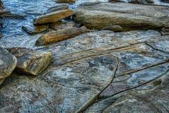 Spiaggia con le vecchie grandi rocce e massi con le crepe nella fine dell'acqua di mare su fotografia stock