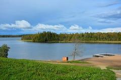Spiaggia del cielo blu, del lago e della foresta sul lago Germantas, Lituania Paesaggio di autunno un giorno pieno di sole fotografia stock libera da diritti