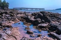 Spiaggia del mare con le rocce ed il fondo del cielo blu immagine stock