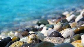 Spiaggia del mare dei peebles con la schiuma delle onde nel moto stock footage