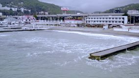 Spiaggia del mare di vista aerea con i frangiflutti Strada del ponte lungo la linea costiera in città archivi video
