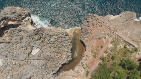Spiaggia del ` s Billabong di angelo, lo stagno naturale sull'isola di Nusa Penida Siluetta dell'uomo Cowering di affari Bali, In stock footage
