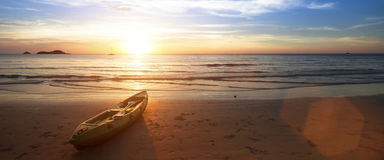 Spiaggia dell'oceano, canoa che si trova sulla riva durante il tramonto meraviglioso Fotografie Stock