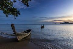 Spiaggia dell'oceano con l'isola e barca su acqua al tramonto in Krabi, Tailandia immagini stock libere da diritti